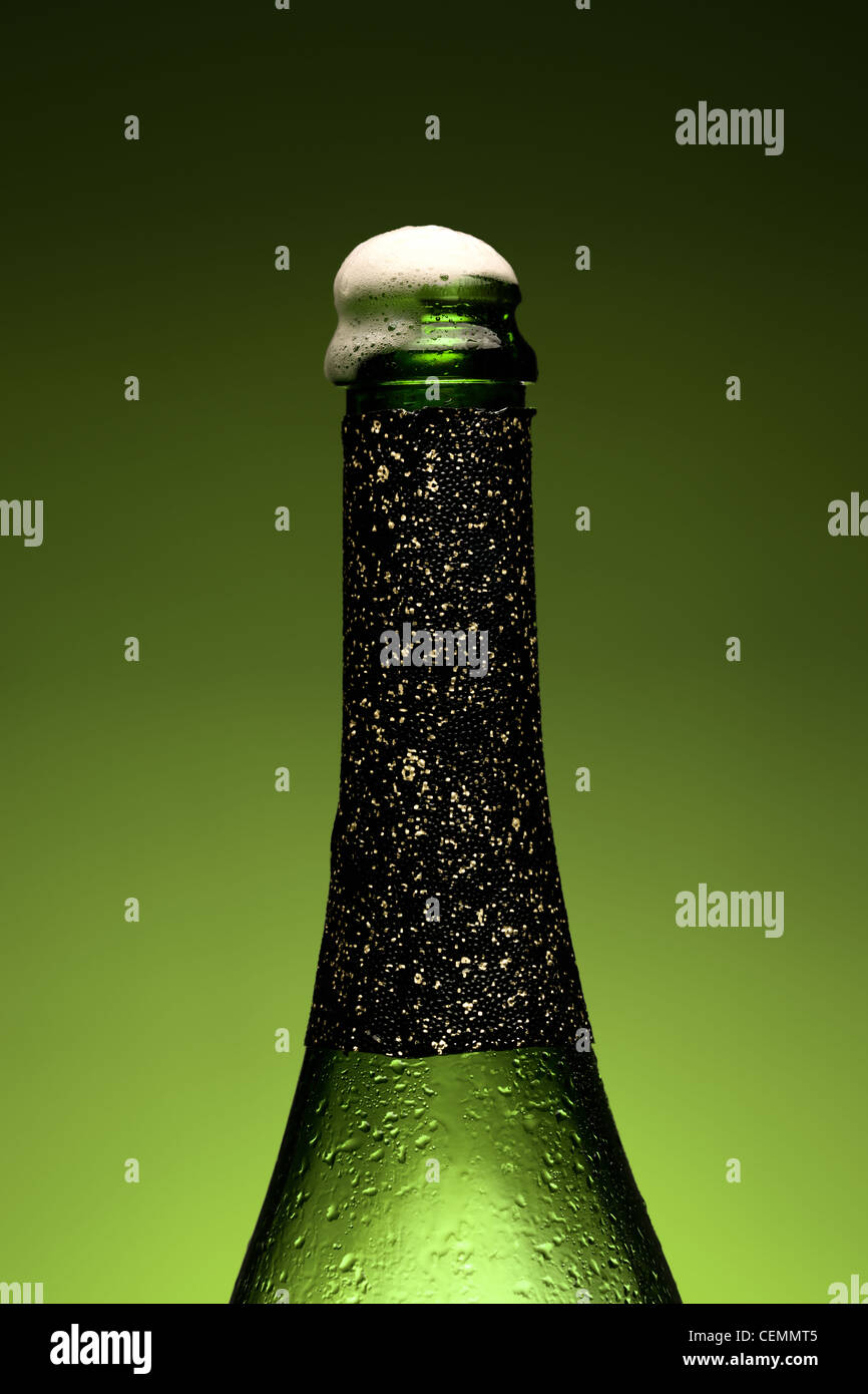 Cold wet bottle of champagne with Froth - Stock Image