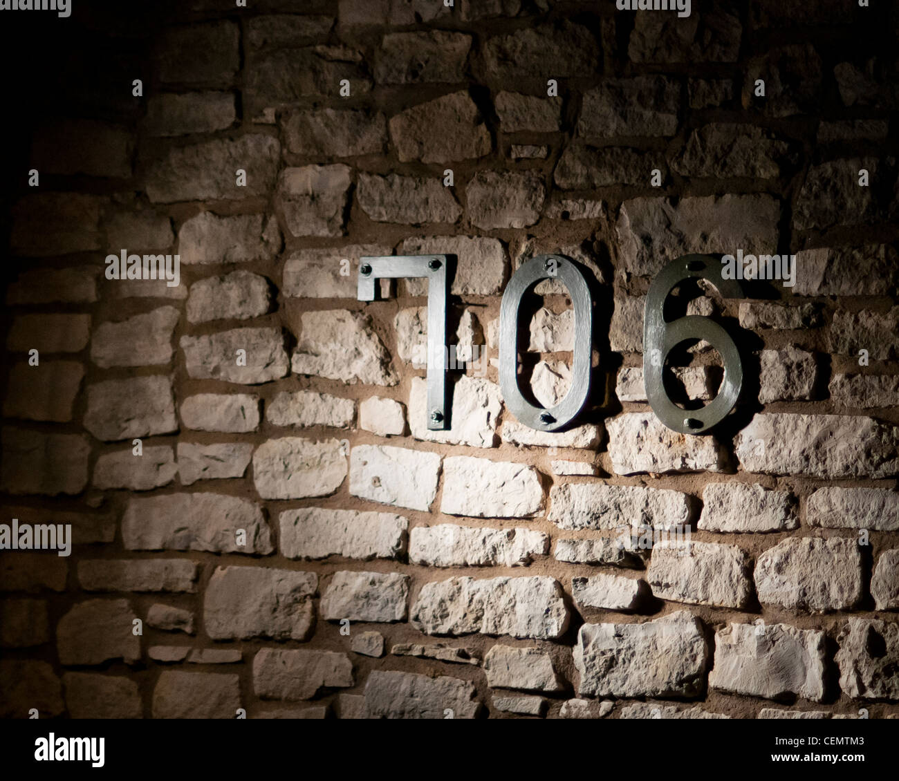 706 building number against rock wall - Stock Image