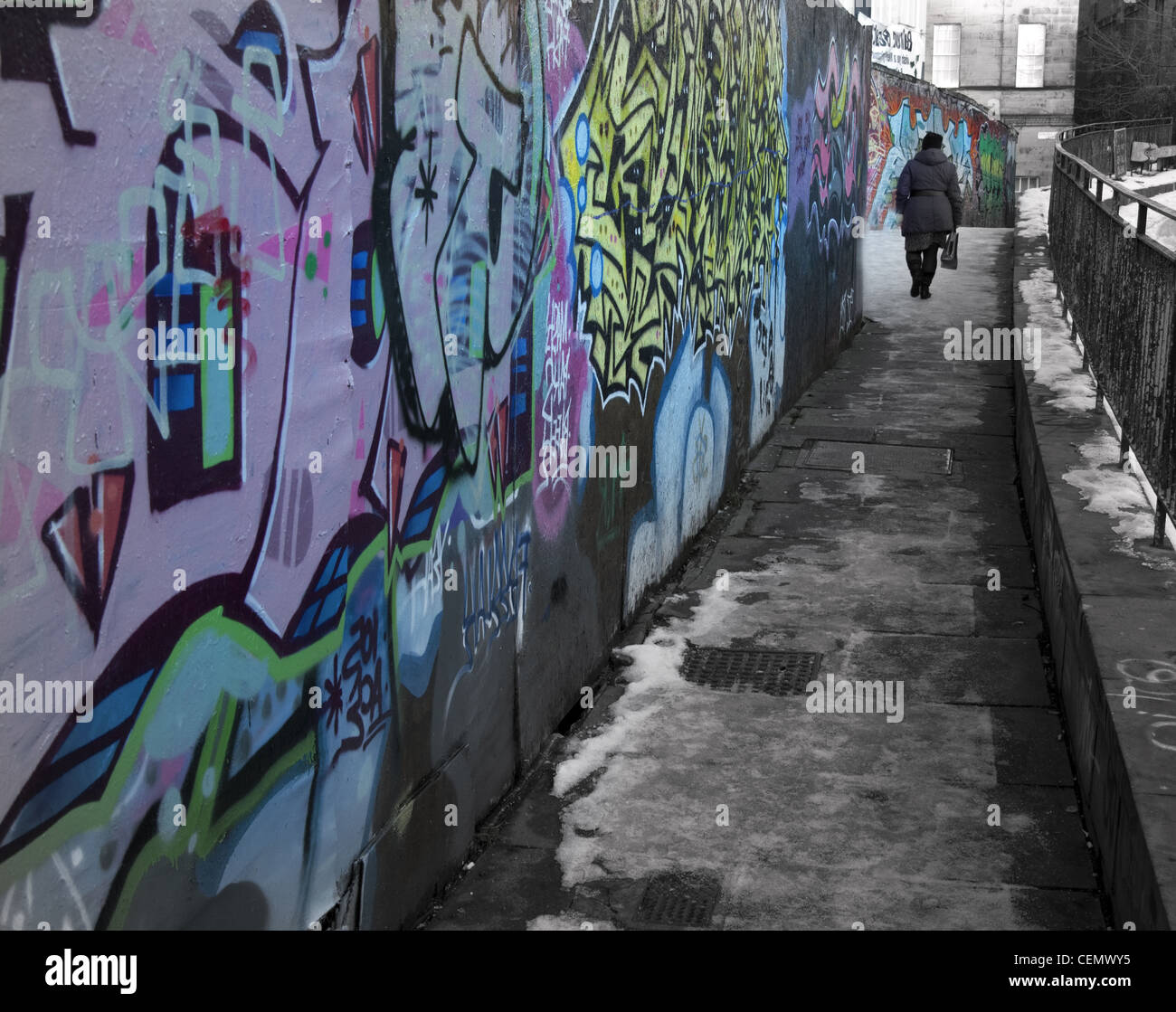 Edinburgh Graffiti and old person inner city scotland. A lonely UK urban street scene in icy winter, snow on the - Stock Image