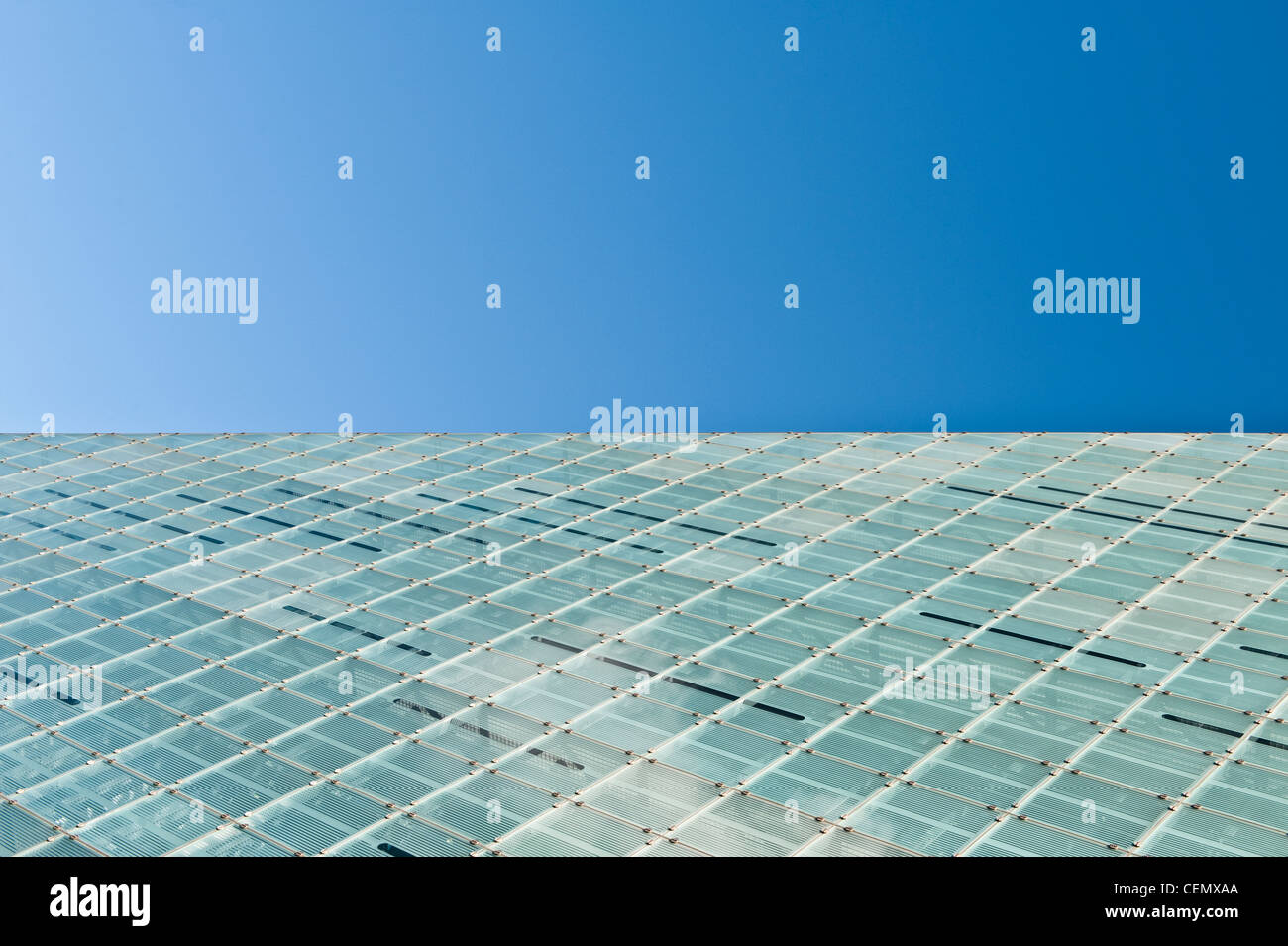 The glass curtain of Urbis centre / National Football Museum in Manchester meets a cloudless clear blue sky. - Stock Image
