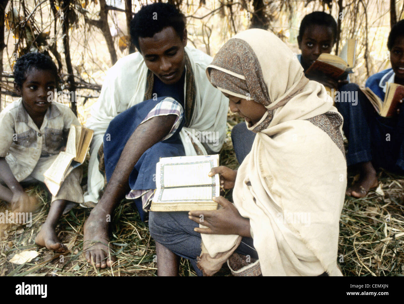 A woman reads the Koran in a refugee camp in Northern Kenya. - Stock Image