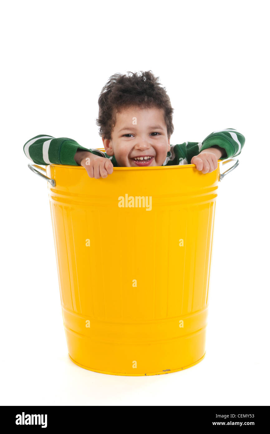 Little boy with black curly hair in yellow trash can isolated over white background - Stock Image