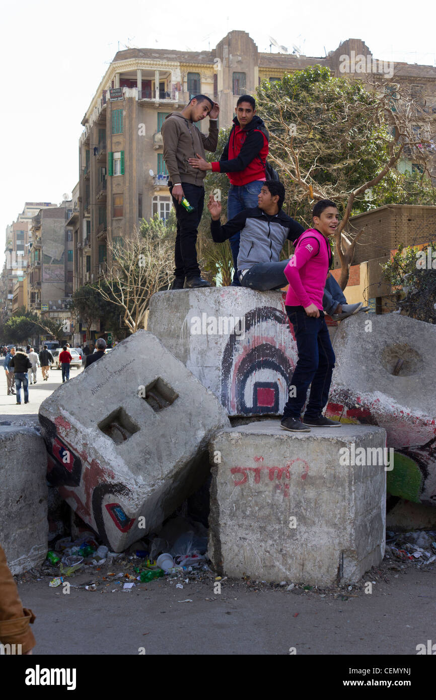 youths posing on top of partially dismantled army barricade, Mohamed Mahmoud street, near Tahrir Square, Cairo, - Stock Image