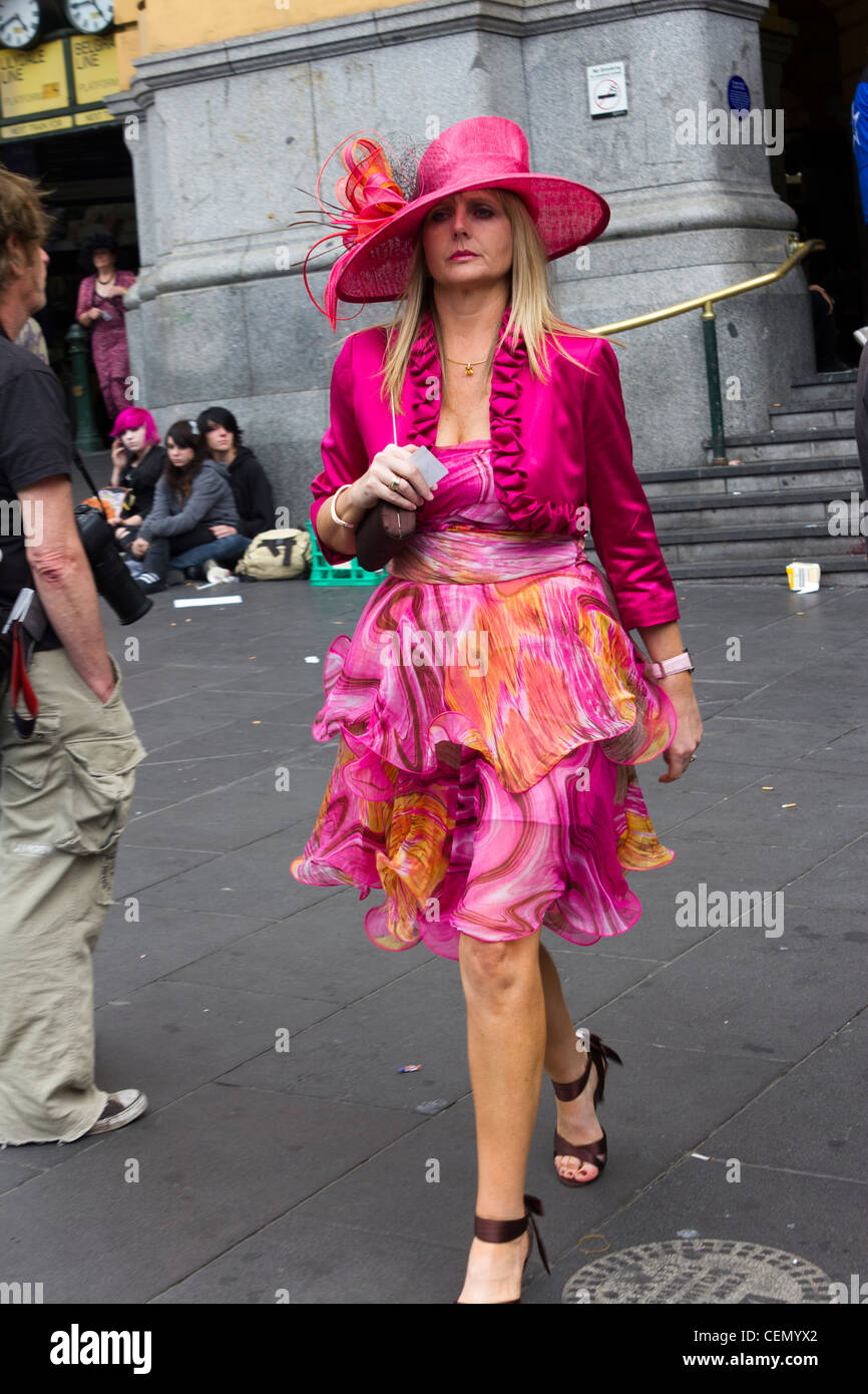 Melbourne cup patron returning from the races, Flinders Street Station, Melbourne, Australia, walking past punks - Stock Image