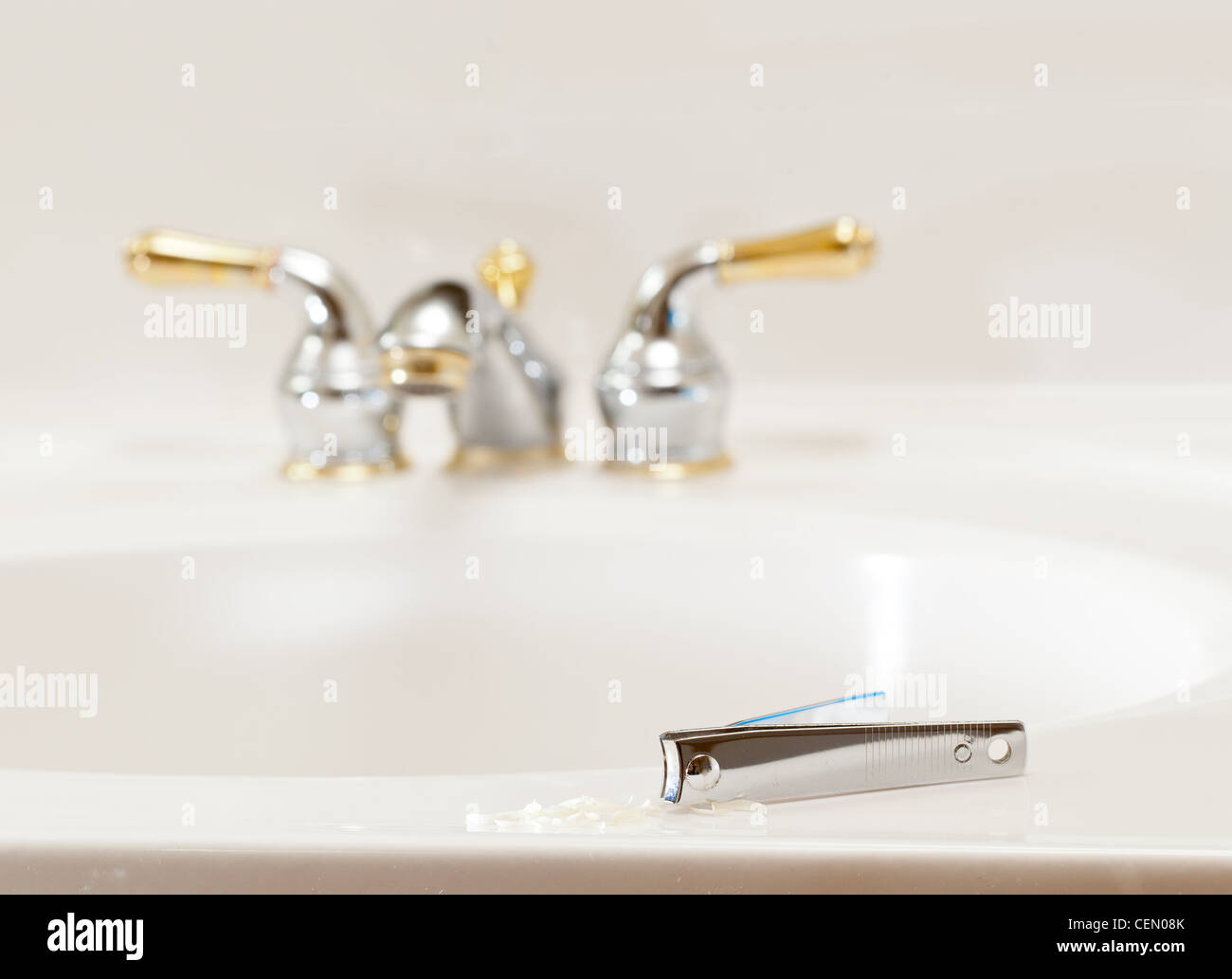 Finger nail clippings on bathroom sink with gold faucets or taps - Stock Image