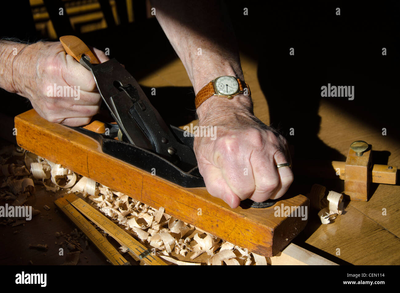 Close up of hands gripping an old wood Block Plane shaving a workpiece to size. Shavings and other old tools are Stock Photo