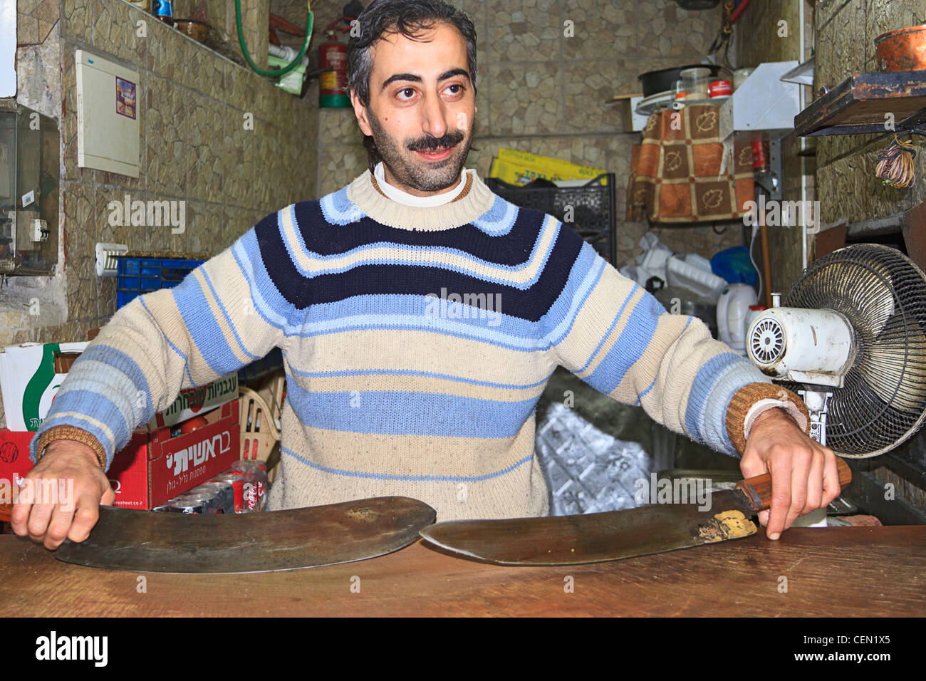 Arab man shows off his kebab knives which are 280 years old. He owns a kebab shop in the Old City of Jerusalem. - Stock Image