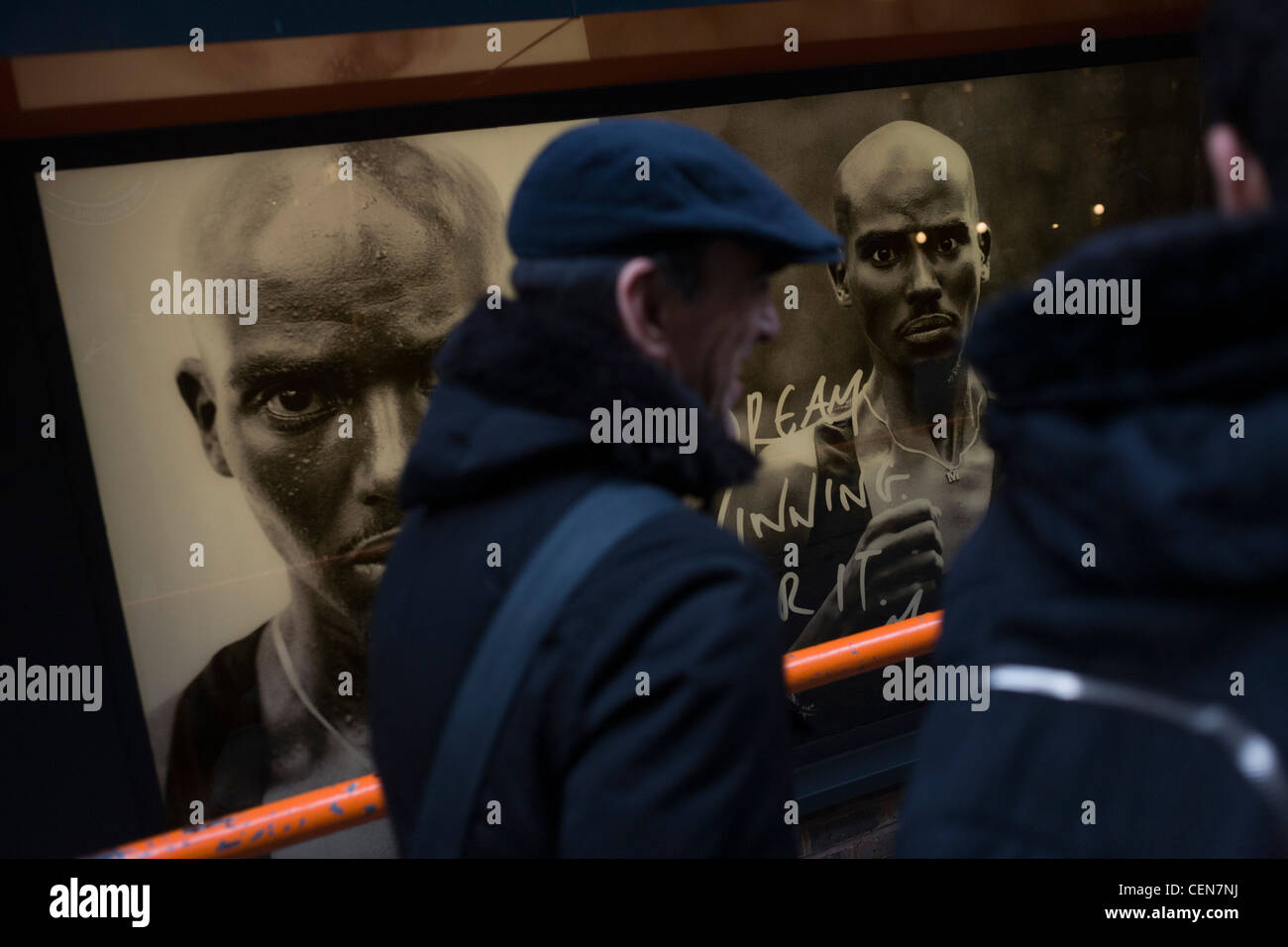 Passers-by walk past British athlete Mo Farah's face adorning posters outside a Nike shop window in London's - Stock Image