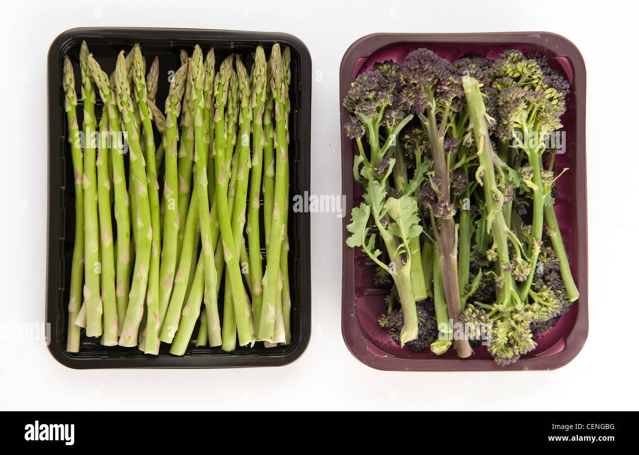 A still life image of asparagus and purple broccoli in black and purple plastic containers - Stock Image