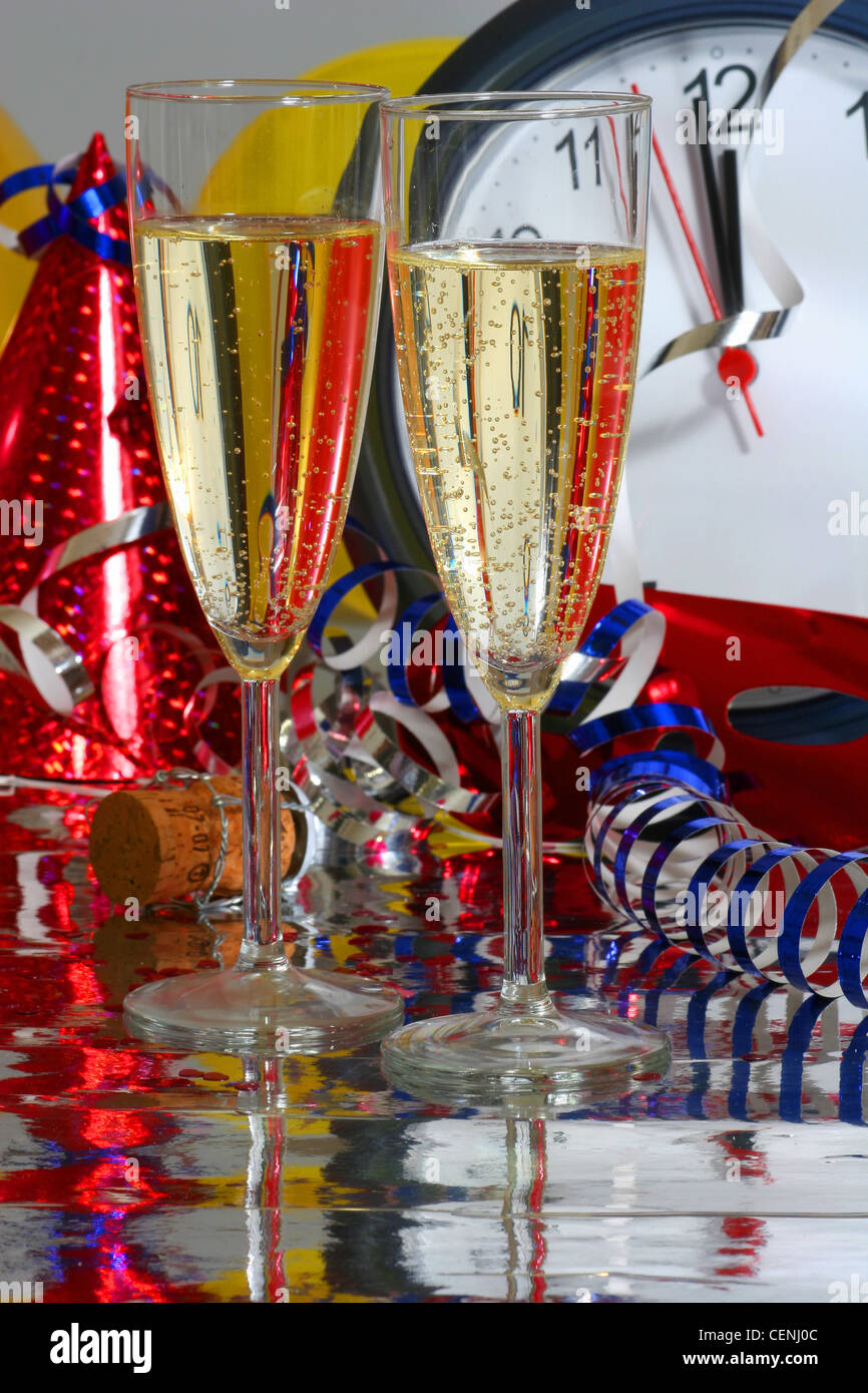 A clock stopped at seconds to midnight, a red metallic party hat next to it, a red mask, metallic blue and gold - Stock Image