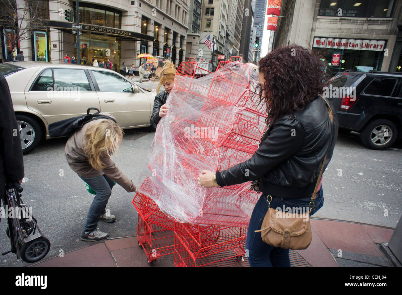 Women attempt to maneuver a cart of baskets through the city streets Stock Photo