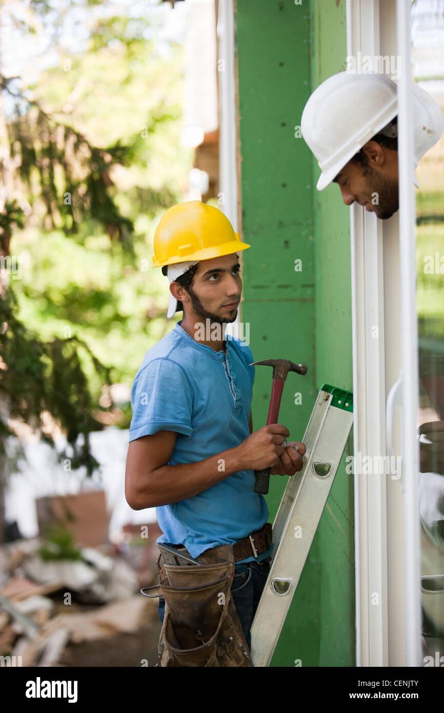 Hispanic carpenter inspecting installation of new window frame - Stock Image