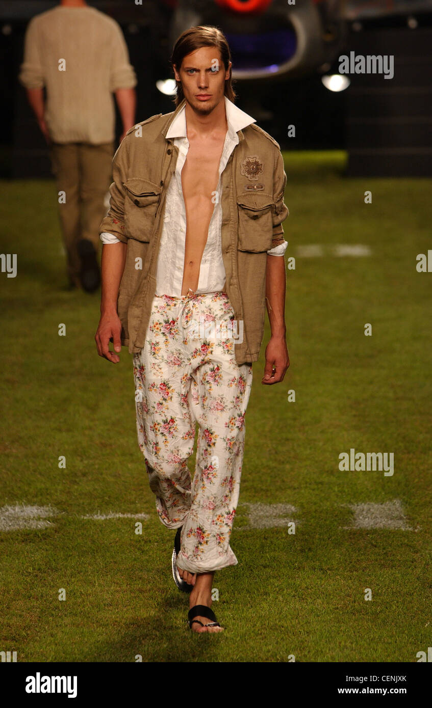 Iceberg Milan Menswear S S Male walking on green grass, wearing olive combat jacket over white shirt and rolled Stock Photo
