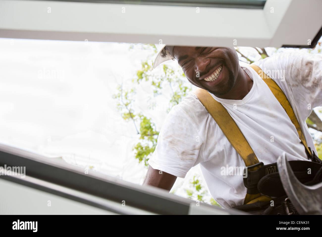Carpenter inspecting installation of skylight window - Stock Image