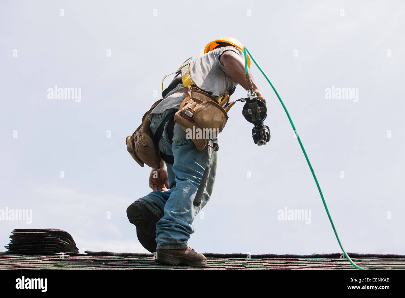 Roofer working on shingling a new roof - Stock Image