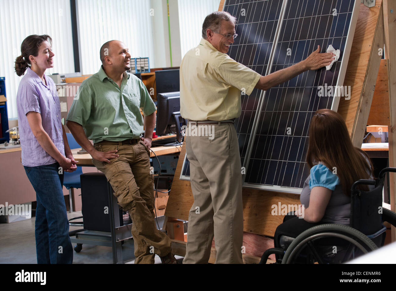Engineering students watching professor cleaning photovoltaic panel to demonstrate improvement in efficiency - Stock Image