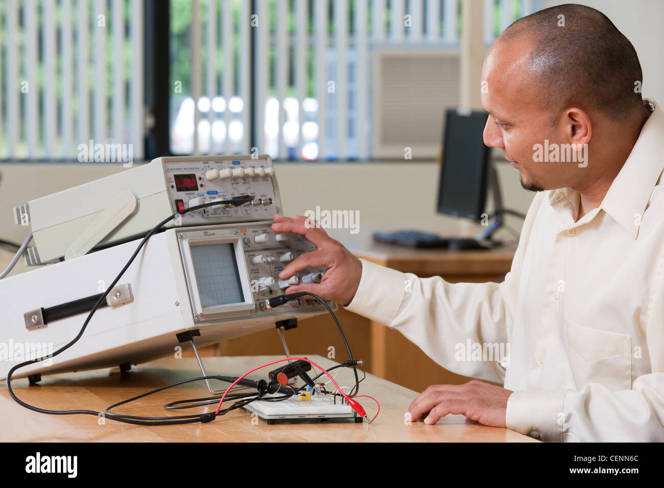 Hispanic engineering student adjusting signal levels on oscilloscope and function generator in a classroom - Stock Image