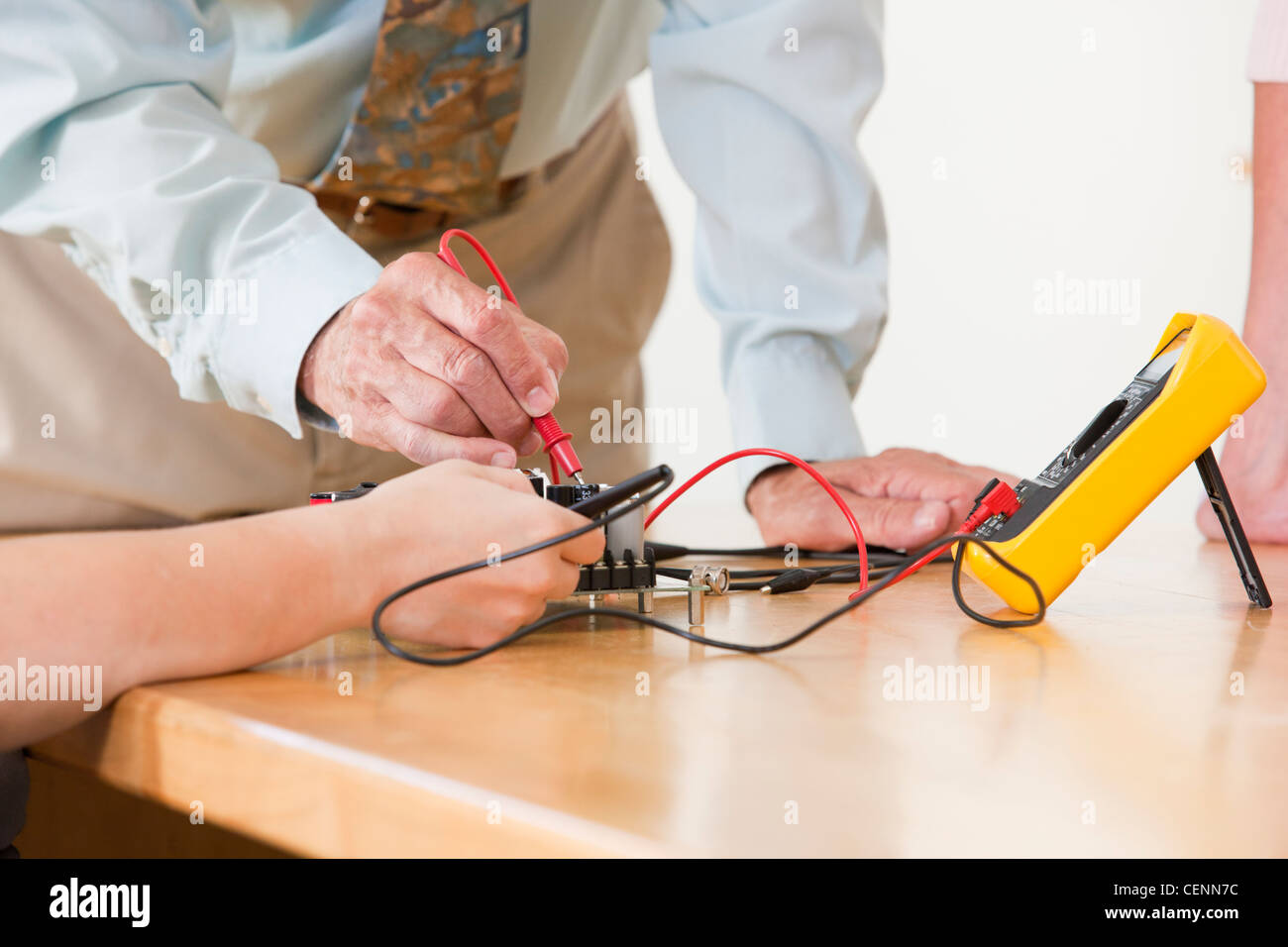 Engineering professor assisting student with multimeter measurement on circuit board - Stock Image