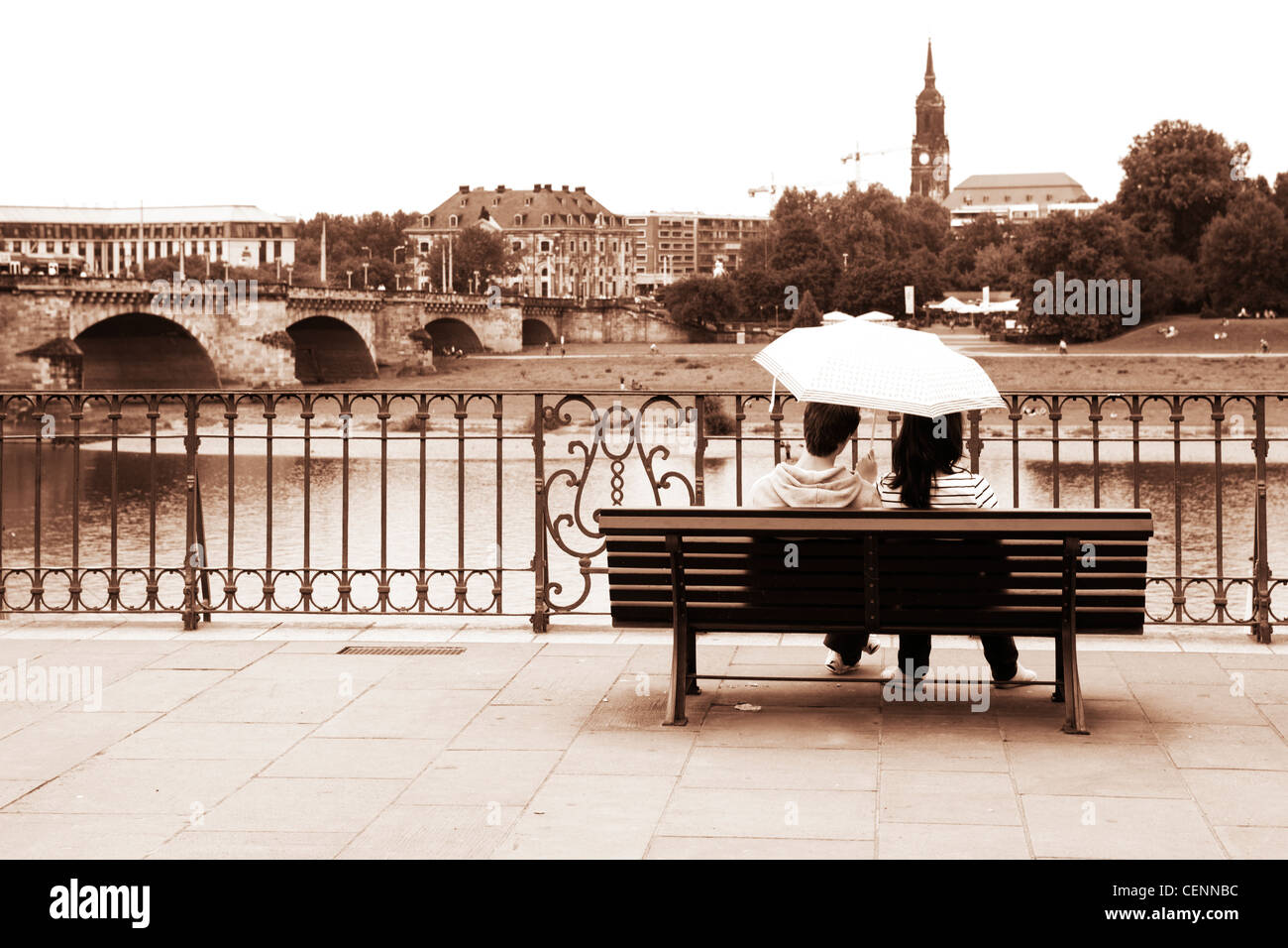 Couple of lovers sitting on a Bench under an umbrella in the rain. Dresden, Saxony, Germany - Stock Image