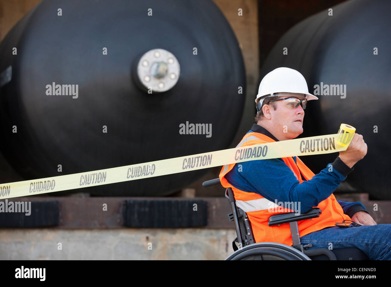 Facilities engineer in a wheelchair pulling caution tape in front of chemical storage tanks - Stock Image