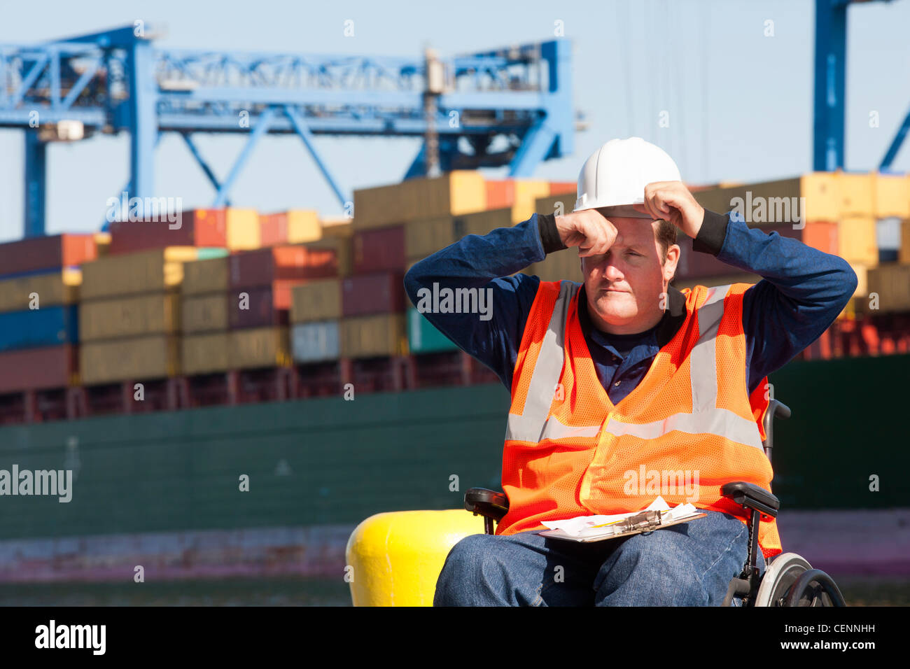 Transportation engineer in a wheelchair recording data for shipping containers and experiencing hot sun Stock Photo