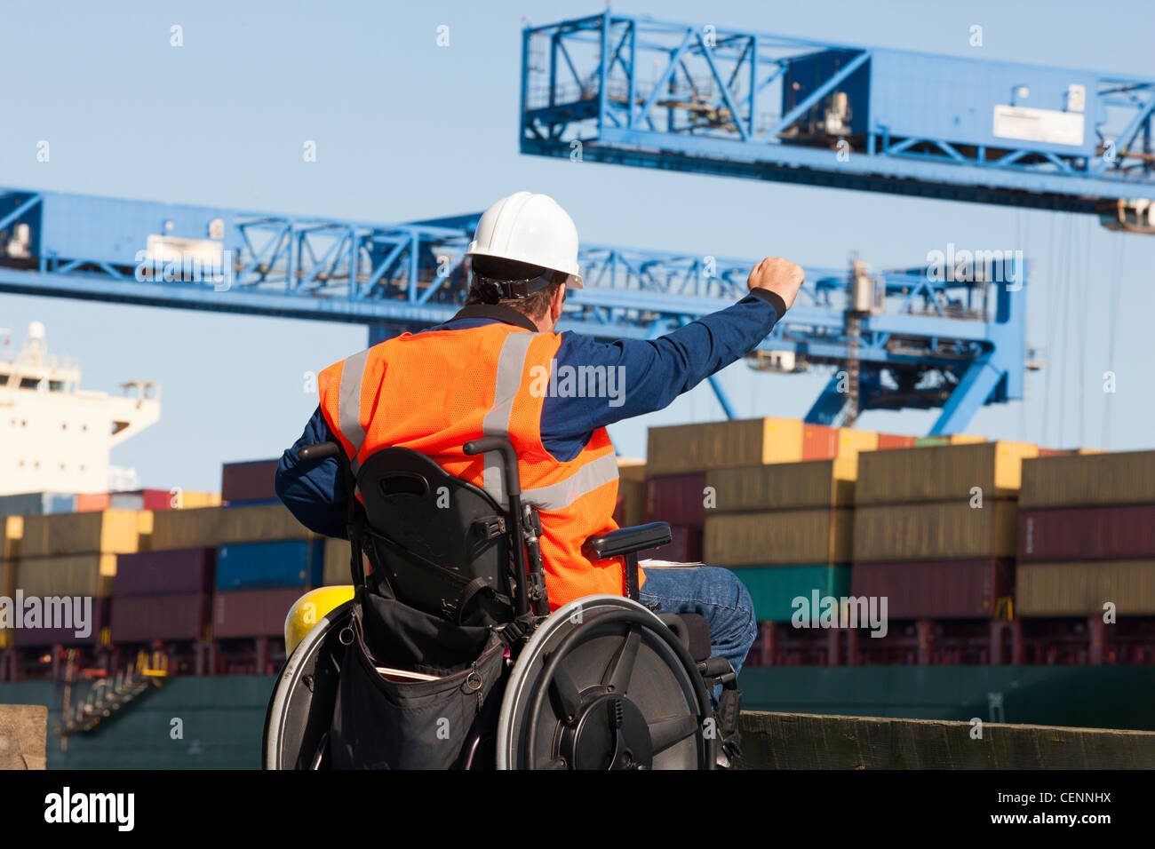 Transportation engineer in a wheelchair giving directions to shipping containers at shipping port - Stock Image