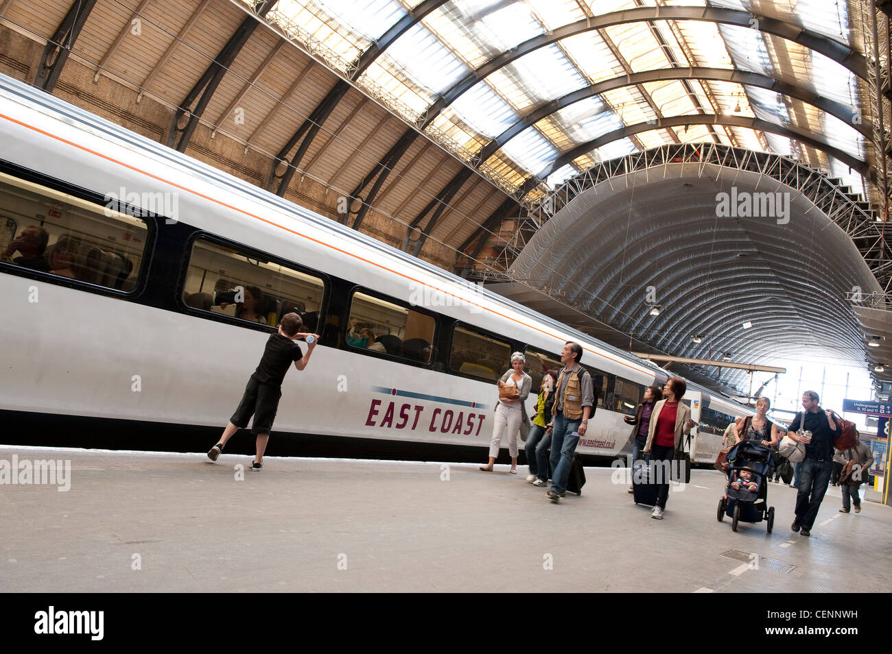 Passengers walking down a platform alongside an East Coast train at a railway station in England. - Stock Image
