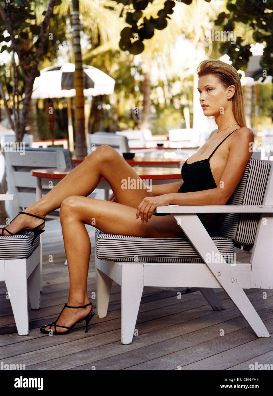 Female dark blonde straight hair worn tucked behind her ears wearing a plain black swimsuit thin straps and strappy - Stock Image