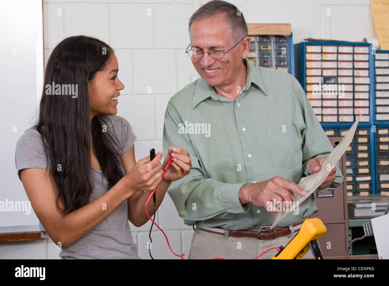 Engineering professor showing a resistor value chart to a student - Stock Image