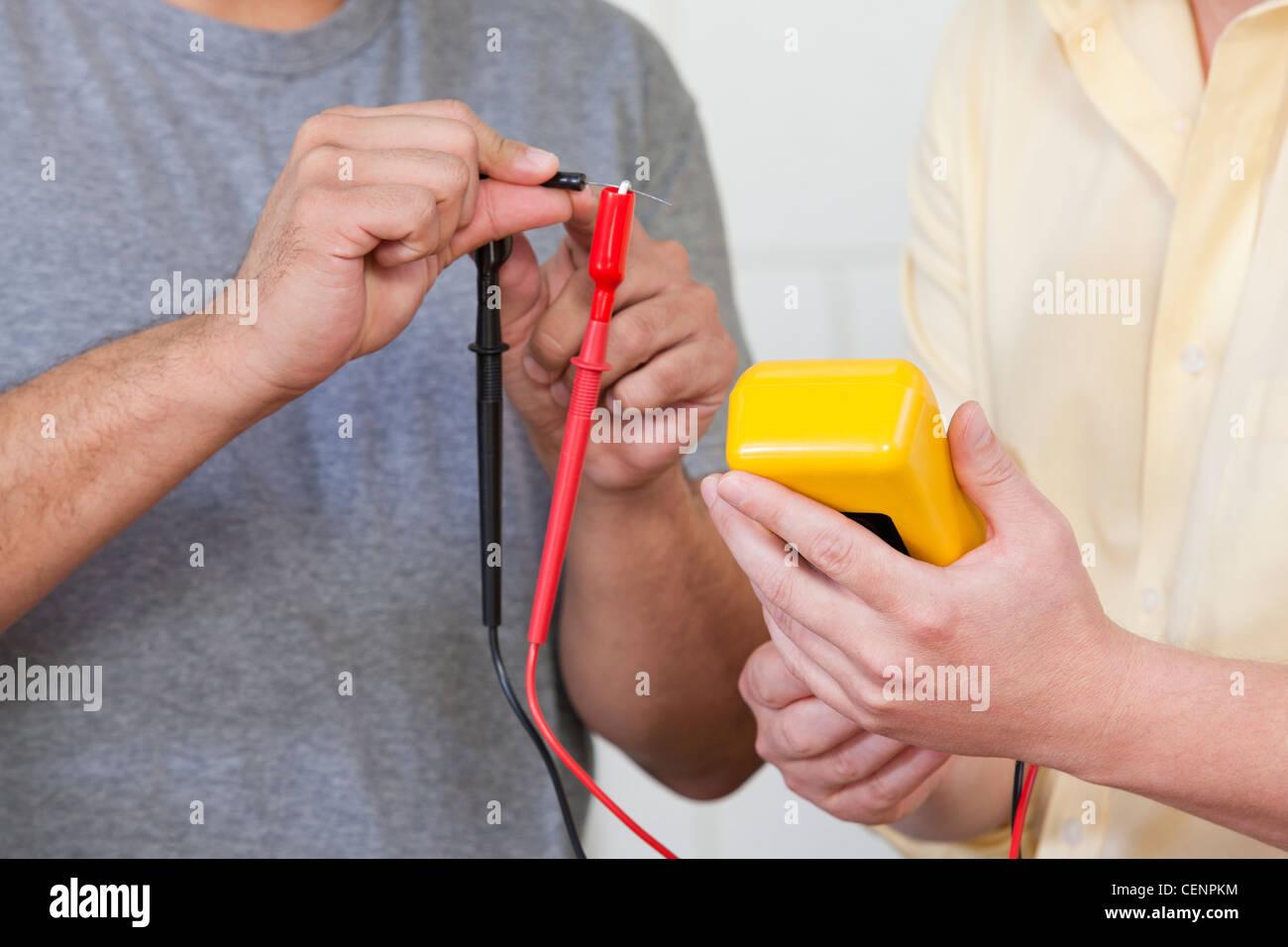 Engineering students measuring resistor using multimeter - Stock Image