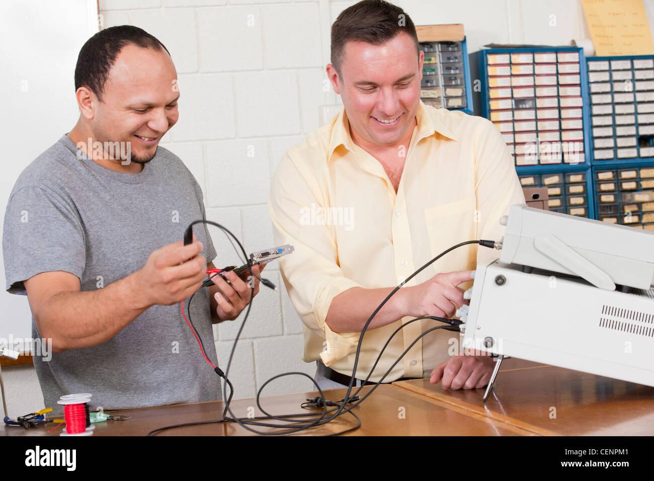 Engineering students using oscilloscope and function generator - Stock Image