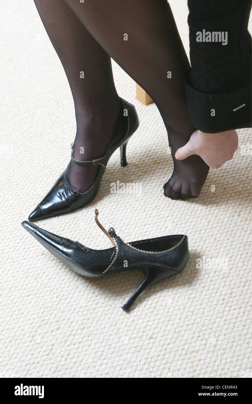 Female wearing black tights, high heeled shoes pointed toes, strap and small buckle Sitting one shoe off, rubbing - Stock Image