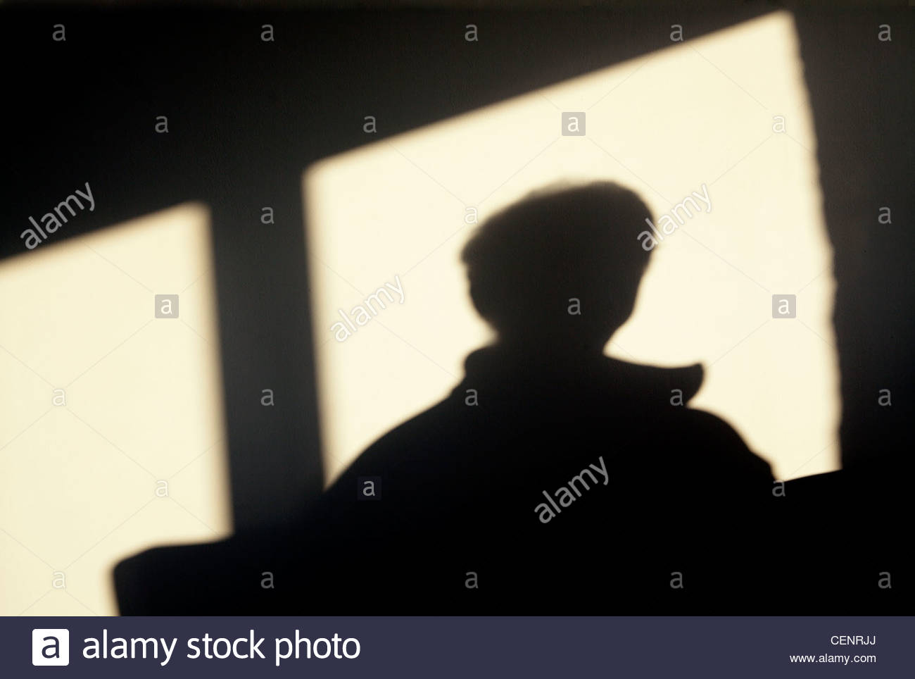 silhouette of a person looking out of a window Stock Photo
