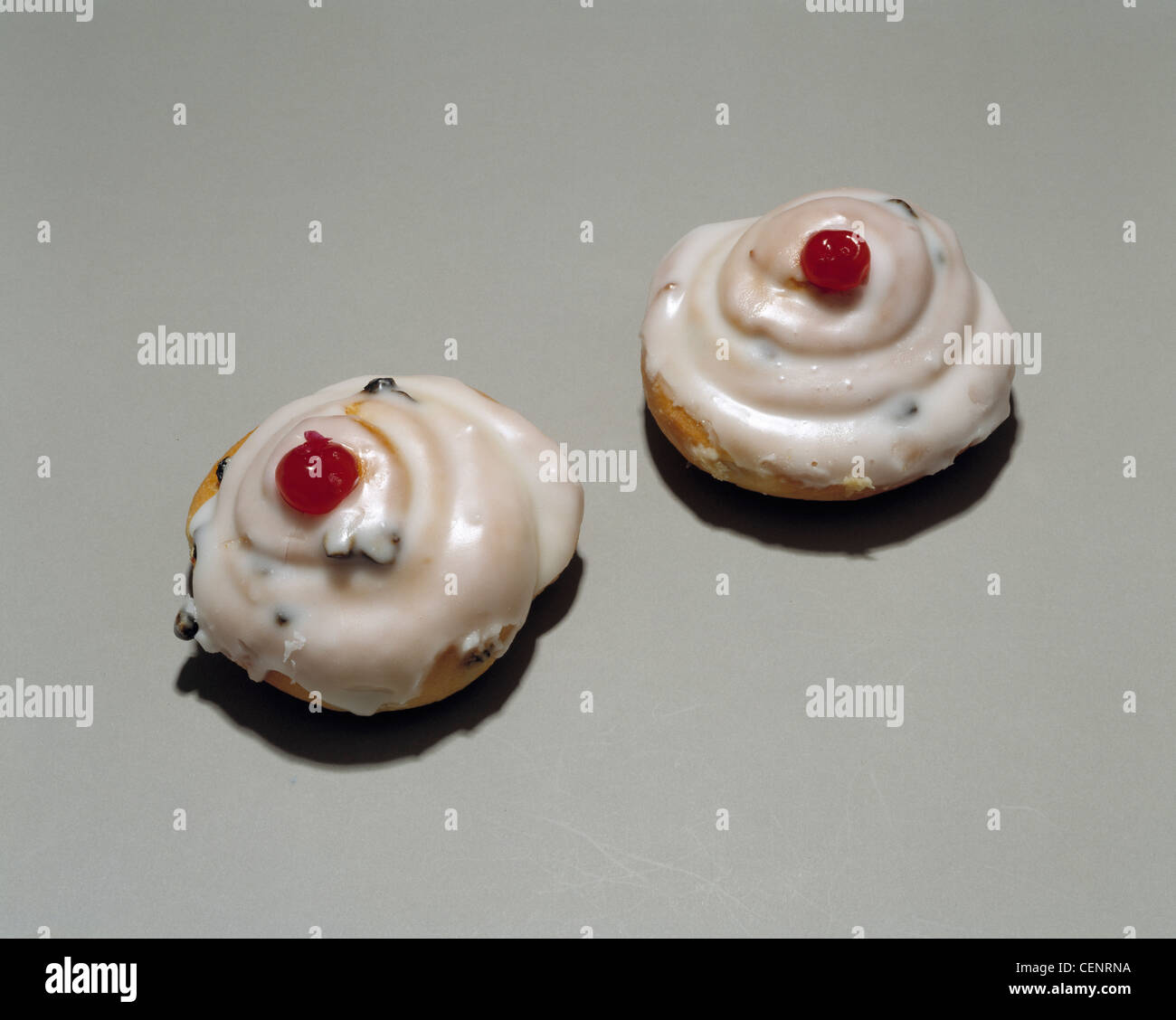 Two cherry buns with a grey background - Stock Image