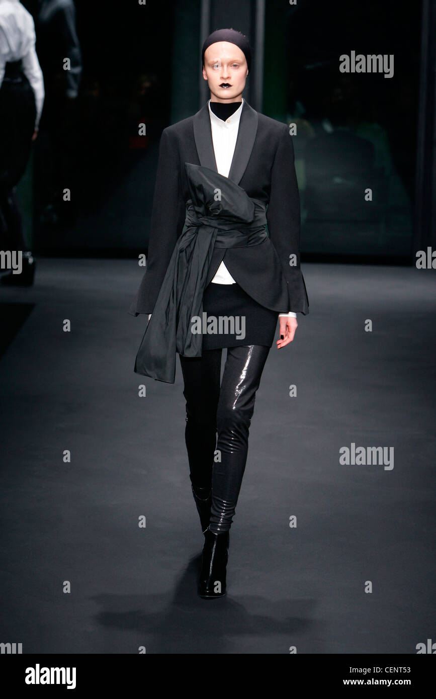 All black dinner jacket big tie bow belt, white shirt short skirt over skinny pants, suede ankle boots, headband - Stock Image