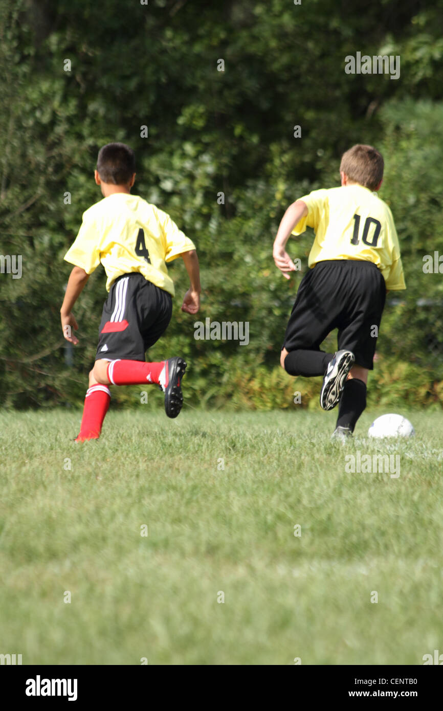 boys Soccer game in sync teammates chasing for ball - Stock Image