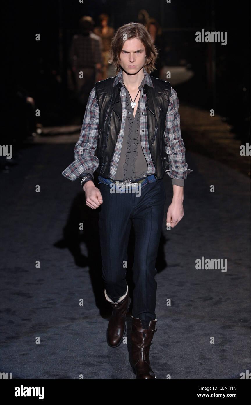 cdc838e16 Gucci Menswear Milan A W Brunette male long hair wearing an open plaid  shirt under a black leather vest a sheer grey blouse