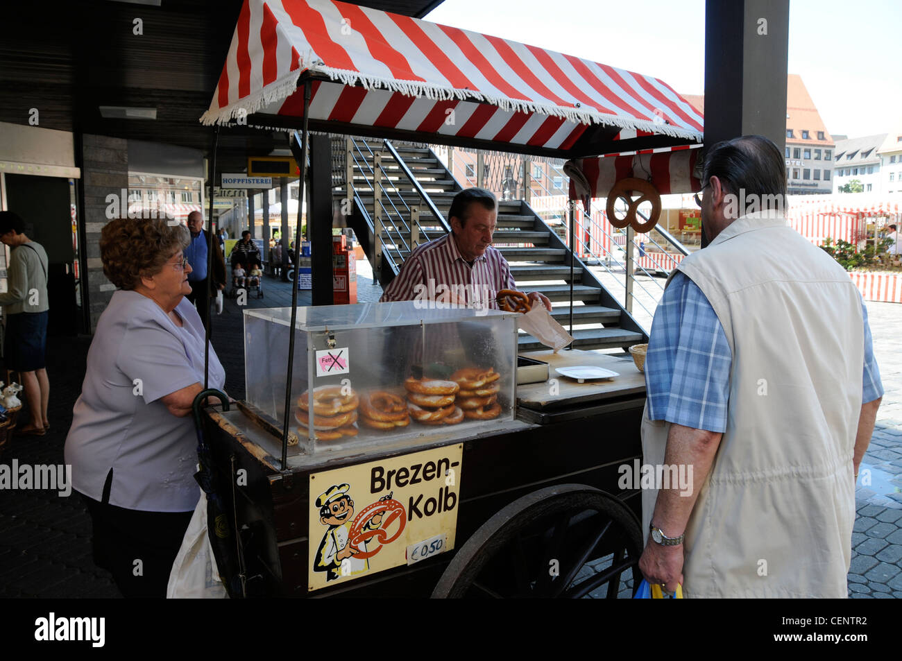A stall holder packing a Brezen for a customer in Nuremberg, Germany - Stock Image