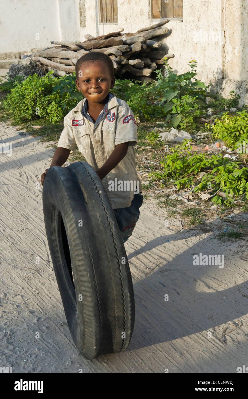 Boy playing with a car tire Bwejuu village east coast of Zanzibar Tanzania - Stock Image