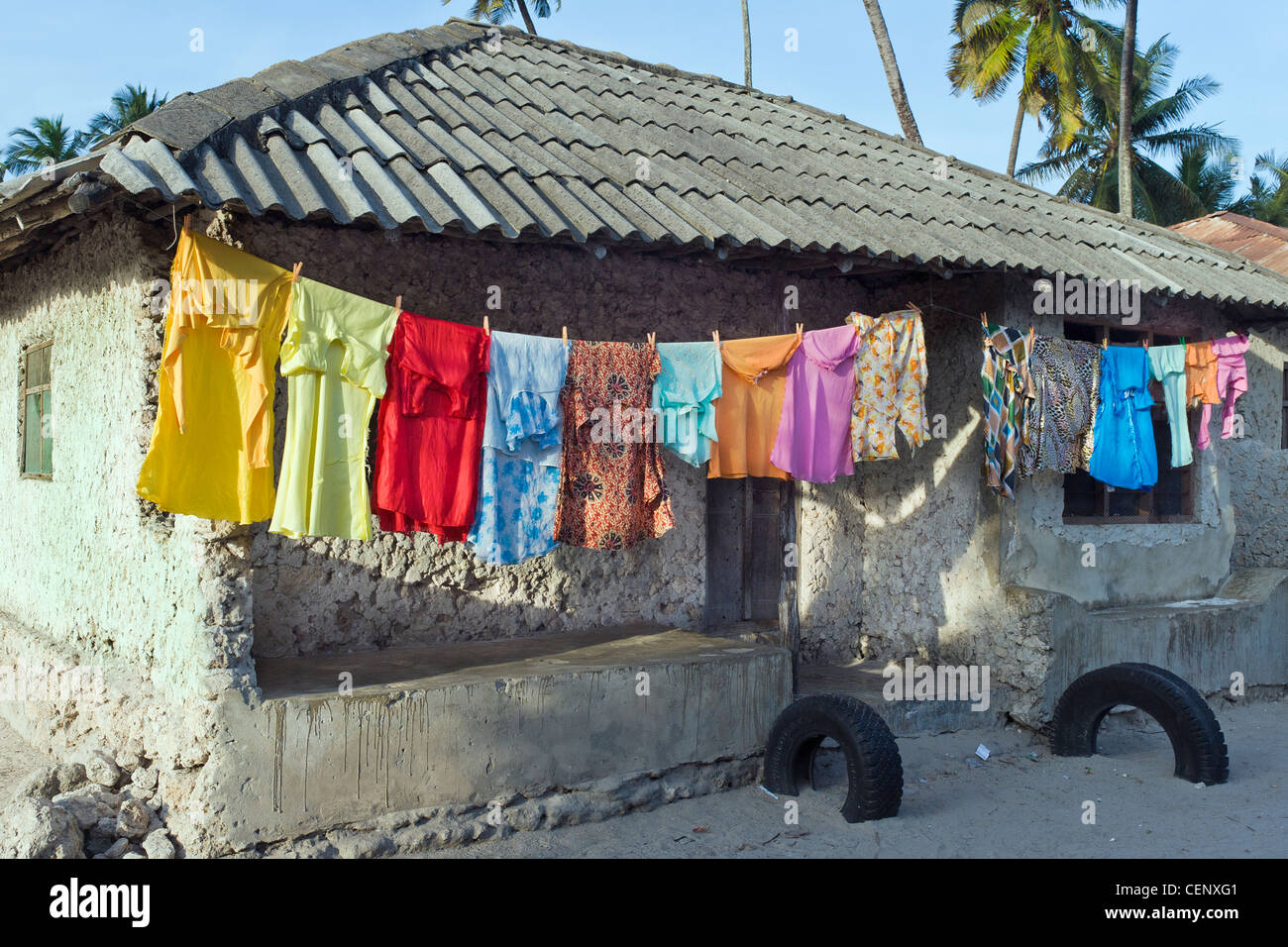 Laundry hanging on a clothesline in front a house in Bwejuu village east coast of Zanzibar Tanzania - Stock Image
