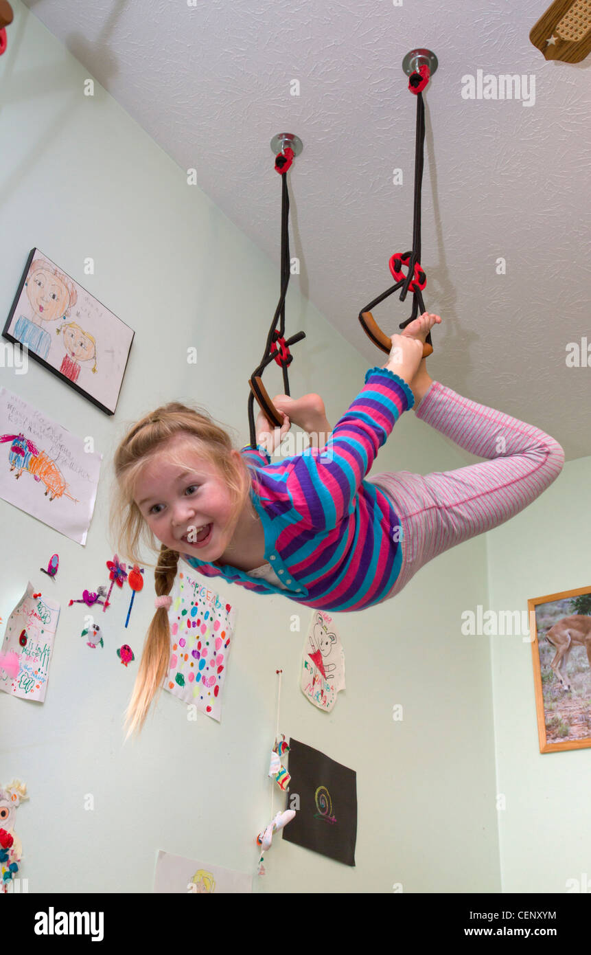 7-years old girl hanging on gymnastic rings in her home room