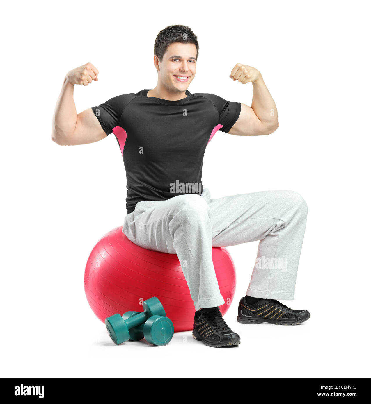 A young bodybuilder gesturing and seated on a pilates ball isolated against white background - Stock Image