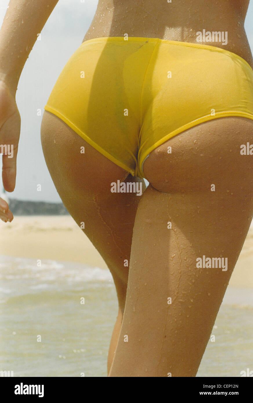 Female wearing yellow bikini bottoms walking on beach Stock Photo