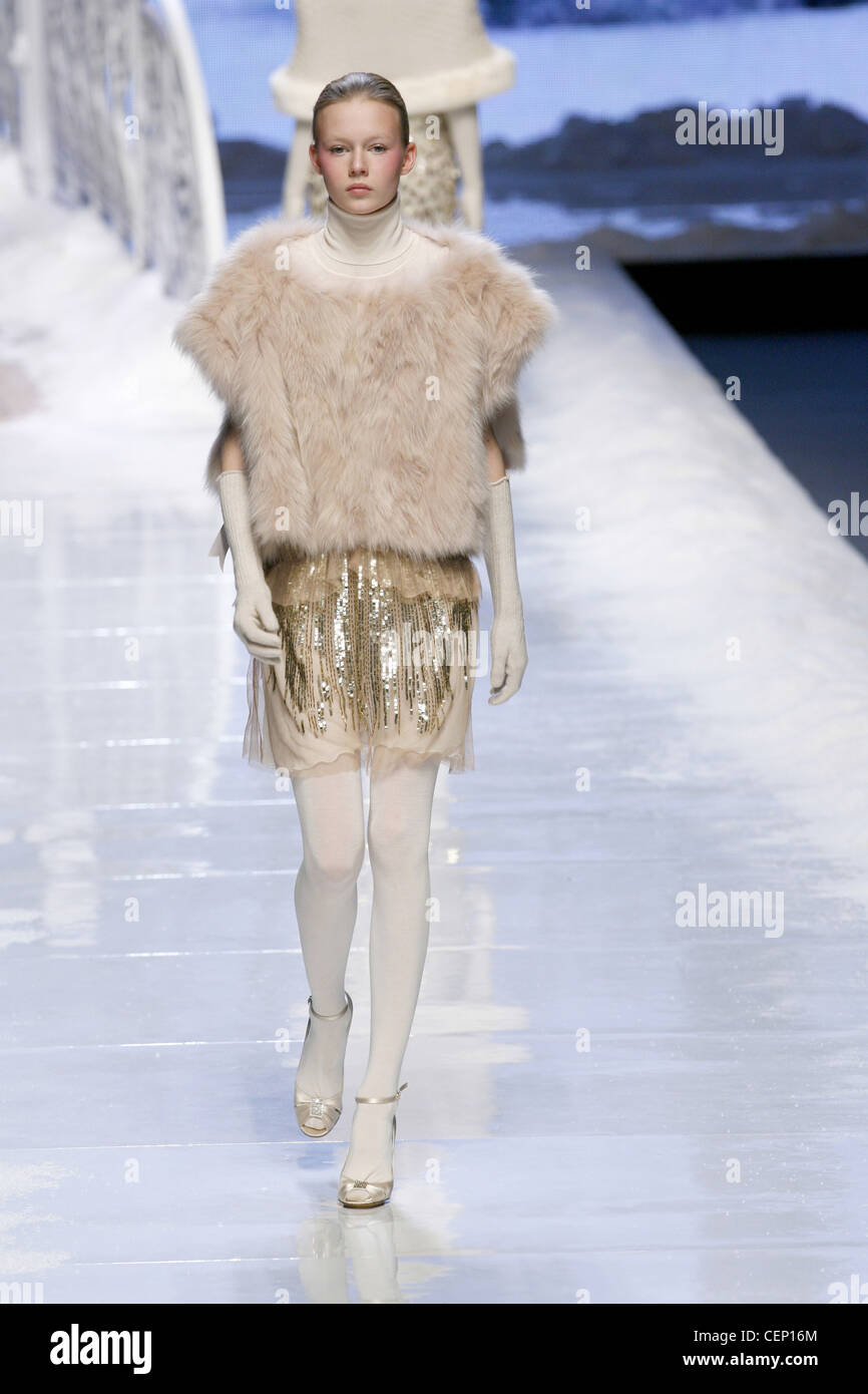 Blu Girl Milan Ready to Wear Autumn Winter Model wearing a fur poncho, cream polo necked top, and short skirt gold - Stock Image