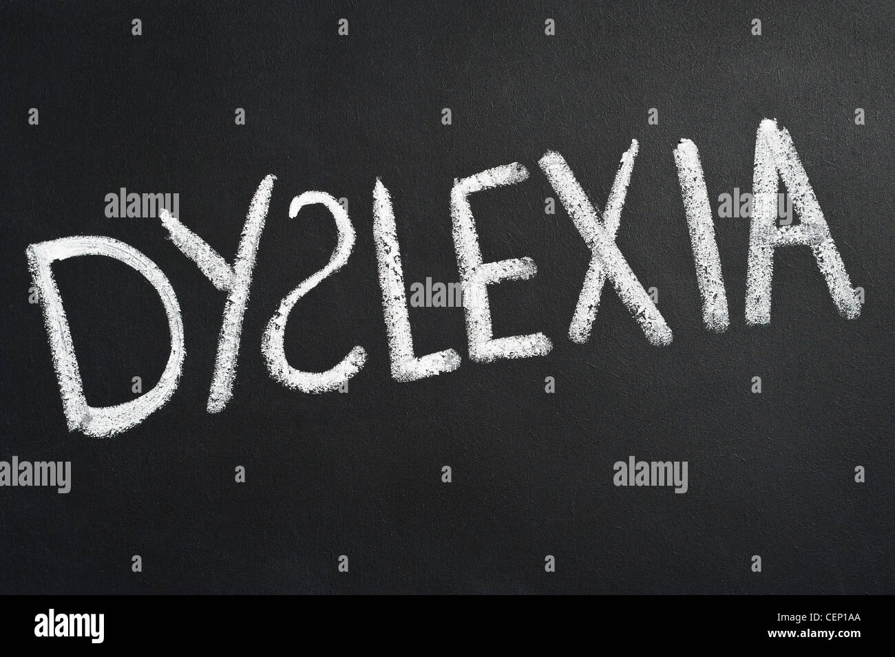 DYSLEXIA CONCEPT. Dyslexia written in chalk on a blackboard with the S facing the wrong way Concept image - Stock Image
