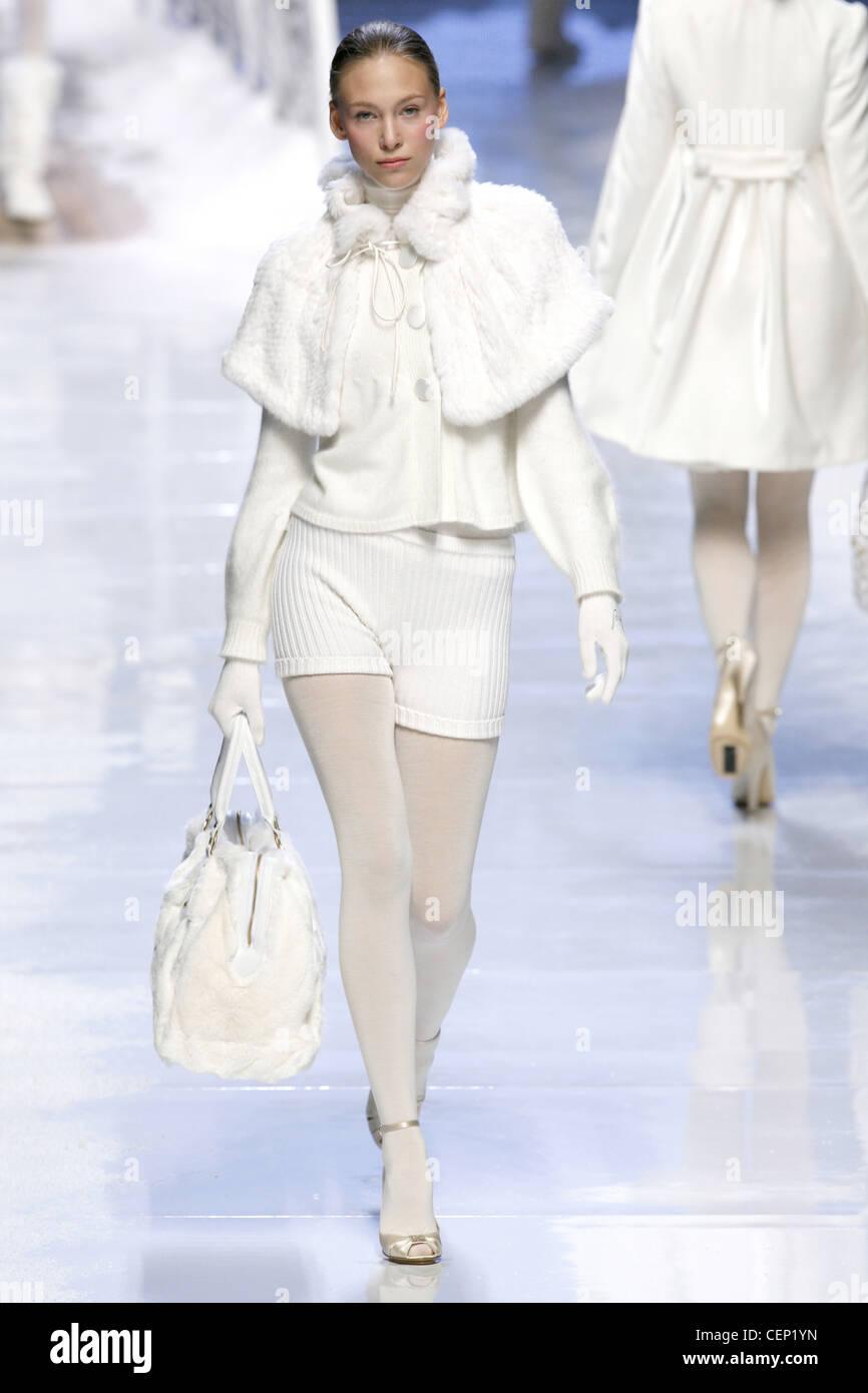Blu Girl Milan Ready to Wear Autumn Winter Model wearing short white fur cape, white high necked jumper button details - Stock Image