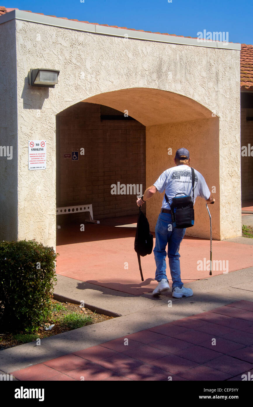 Using two canes, a crippled man enters a Southern California gymnasium for rehabilitation therapy. - Stock Image