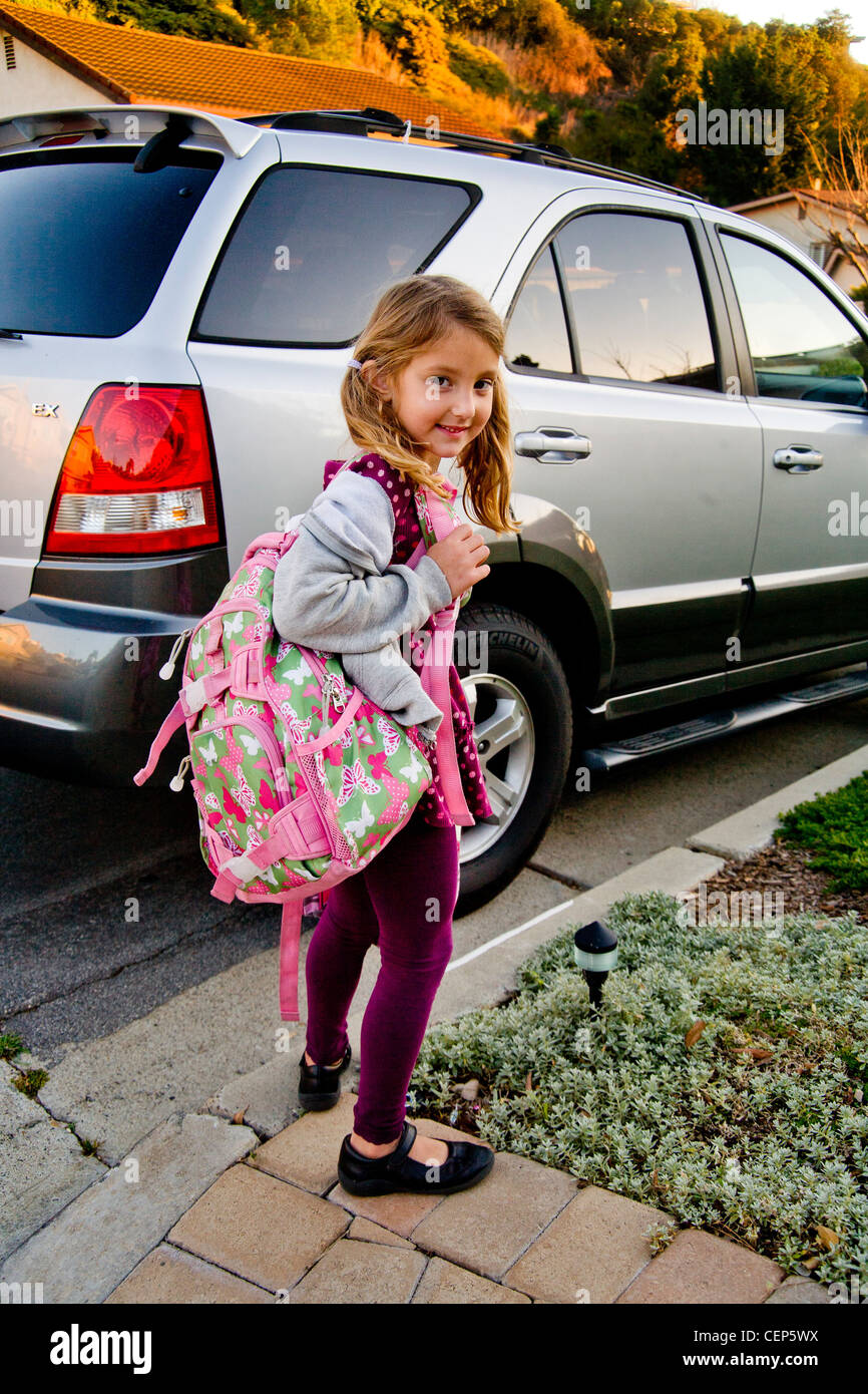 Carrying her backpack and lunch box, a 6 year old girl waits by the car to go to school in San Juan Capistrano CA. - Stock Image