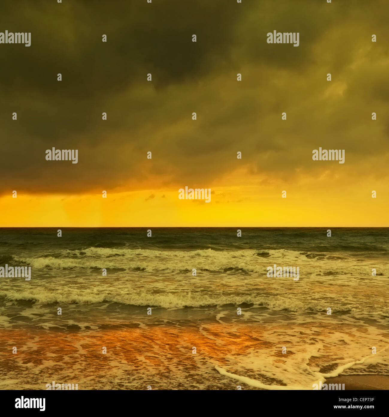 waves breaking on a wintery beach at dawn; spain - Stock Image