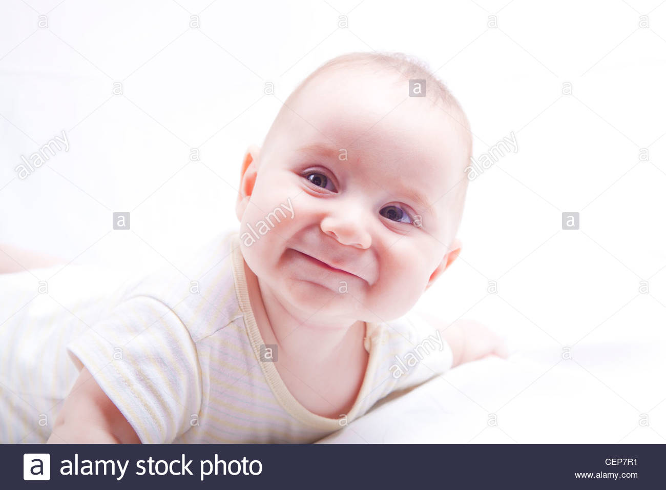 Cute Baby Boy Smiling While He Lays Down On White Background Stock
